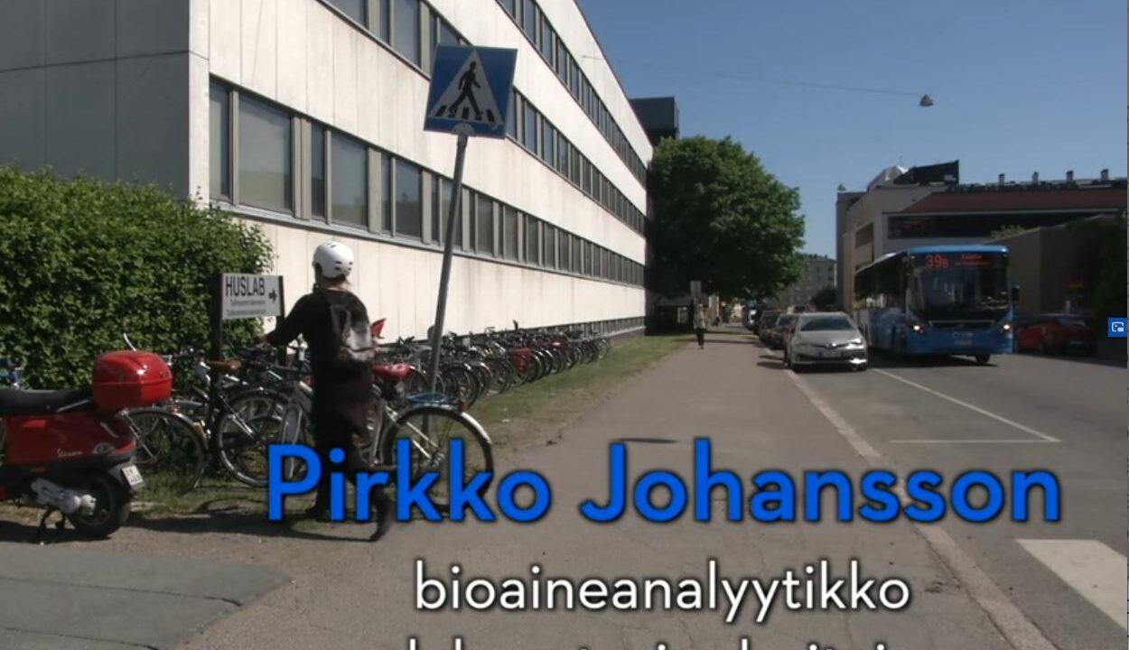 Nainen jättää pyörää pyörätelineeseen.
