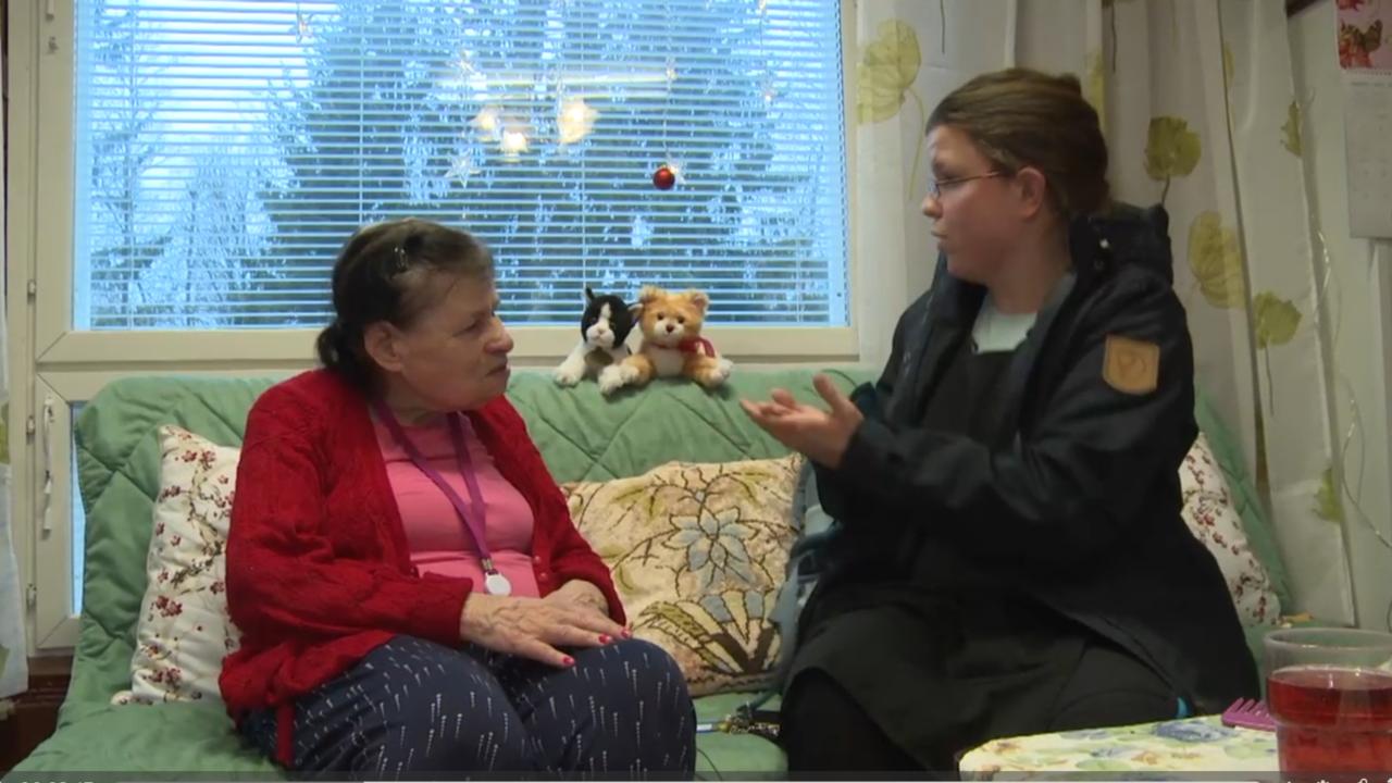 Vanha nainen istuu sohvalla ja katsoo vieressä istuvaa naista, joka viittoo viittoman auttaa.