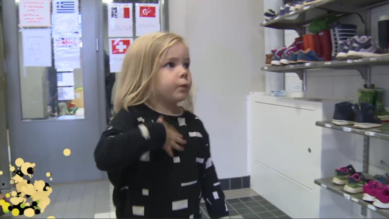 Pikkutyttö seisoo eteisessä katsoo kenkiä ja viittoo viittoman mun.