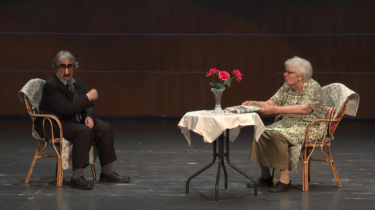 Esiintymislavalla on pöytä ja kaksi tuolia, tuoleissa istuu nainen ja mieheksi pukeutunut nainen.