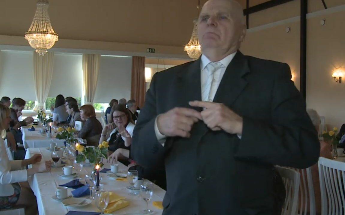Iäkäs mies seisomassa, taustalla juhlapukuisia ihmisiä istumassa ruokapöytien ääressä.