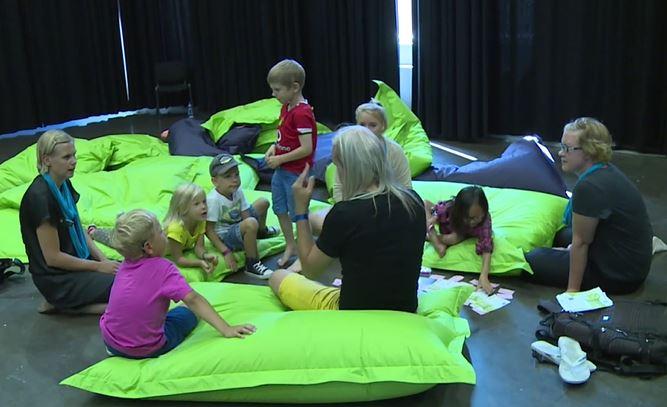 Ryhmä lapsia ja aikuisia istuu lattialla tyynyjen päällä.
