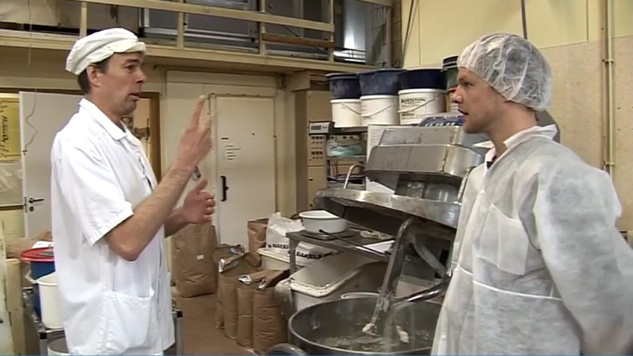 Kaksi miestä, leipurin vaatteet päällä keskustelevat viittoen leipomossa.
