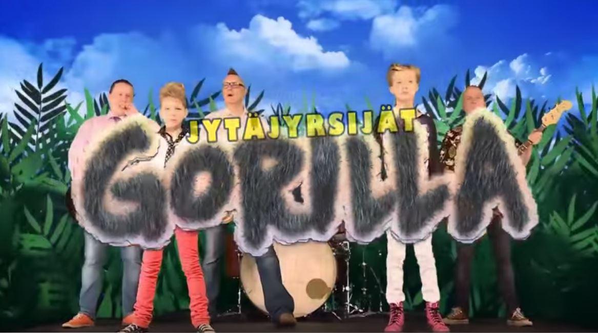 Bändin jätkät ja viittojat ja kuvan päällä videon nimi kirjoitettuna.