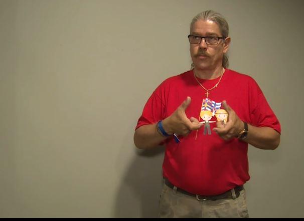 Mies punaisessa paidassa viittomassa.