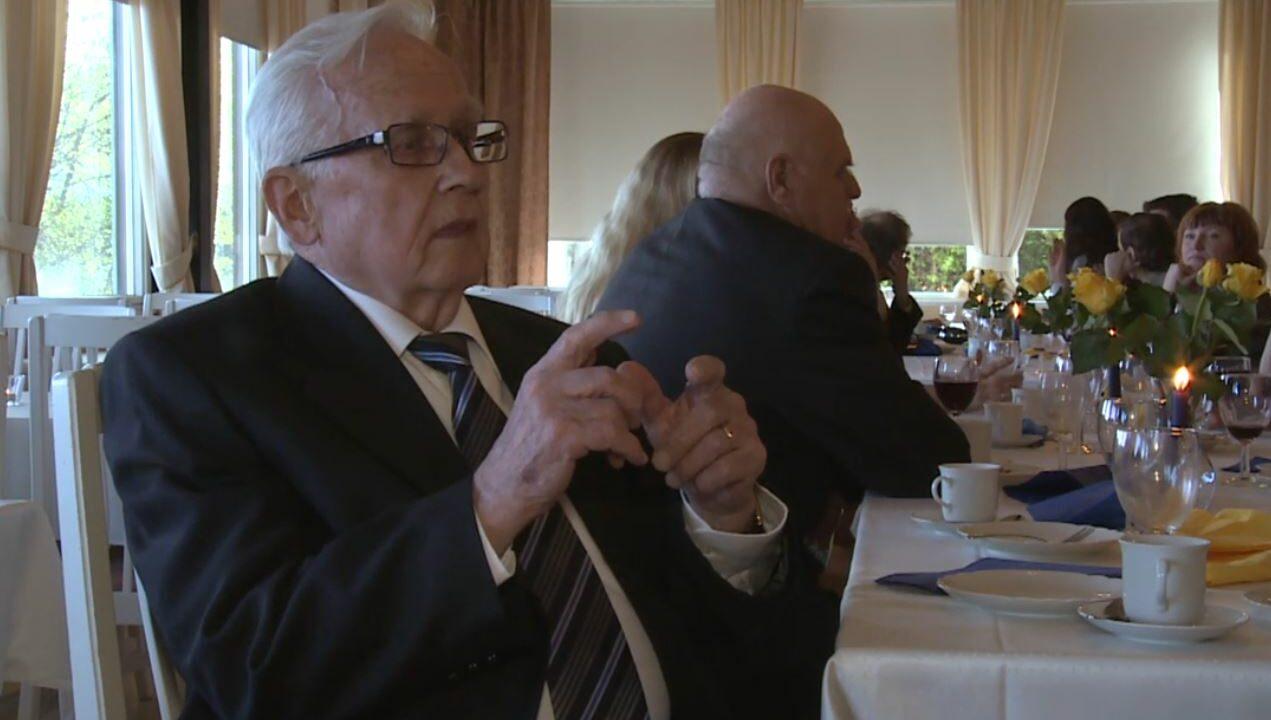 Iäkäs mies istuu pöydän ääressä, taustalla näkyy juhlapukuisia ihmisiä istumassa.