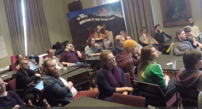 Ryhmä nuoria istuu rennosti isossa salissa.
