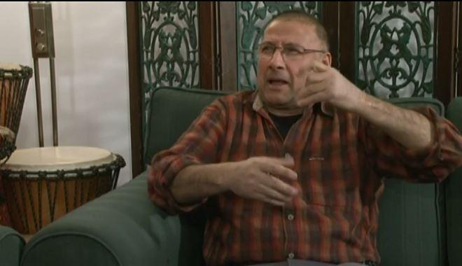 Mies, ruskearaitainen kauluspaita, kädet koholla rinnan kohdalla viittomassa.