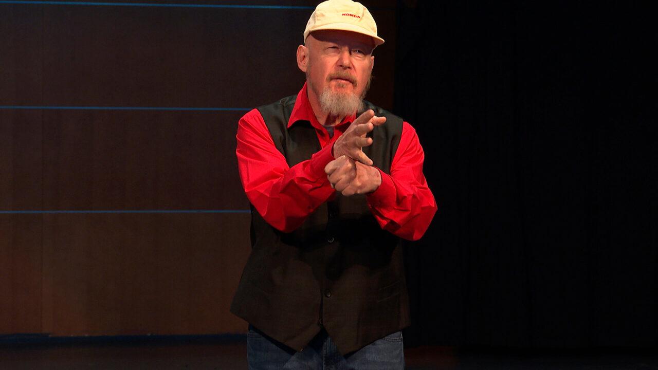 Mies punaisessa paidassa ja valkoisessa lippiksessä viittoo esiintymislavalla.