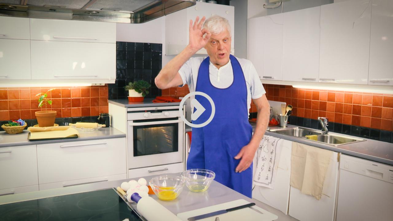Mies seisoo keittiössä, katsoo kameraan ja viittoo
