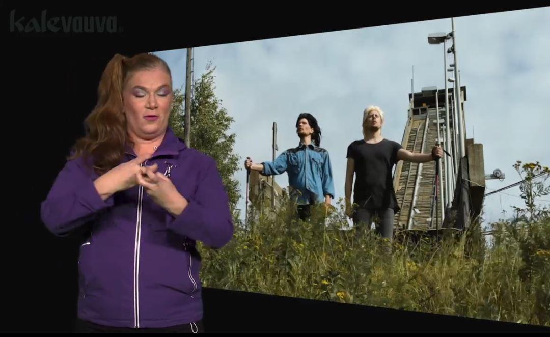 Kaksi miestä seisoo keskellä luontoa, vasemmassa reunassa nainen viittoo KOUVOLA.