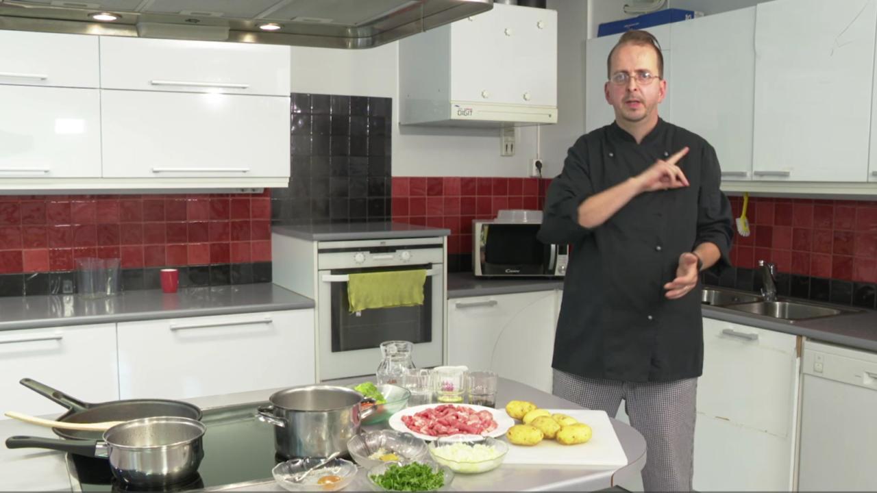 Mies kokki seisoo keittiössä ja viittoo katsoen kameraa