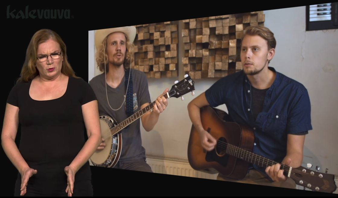 Kaksi miestä soittaa kitaraa, vasemmassa reunassa nainen viittoo SYNNYTYS.