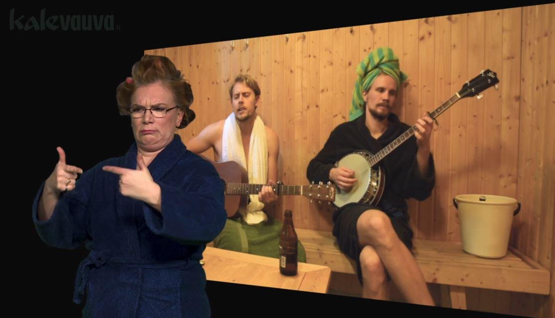 kaksi miestä istuu saunan pukuhuoneessa soittamassa banjoa ja kitaraa, vasemmassa reunassa nainen viittoo TELAKOITUA.