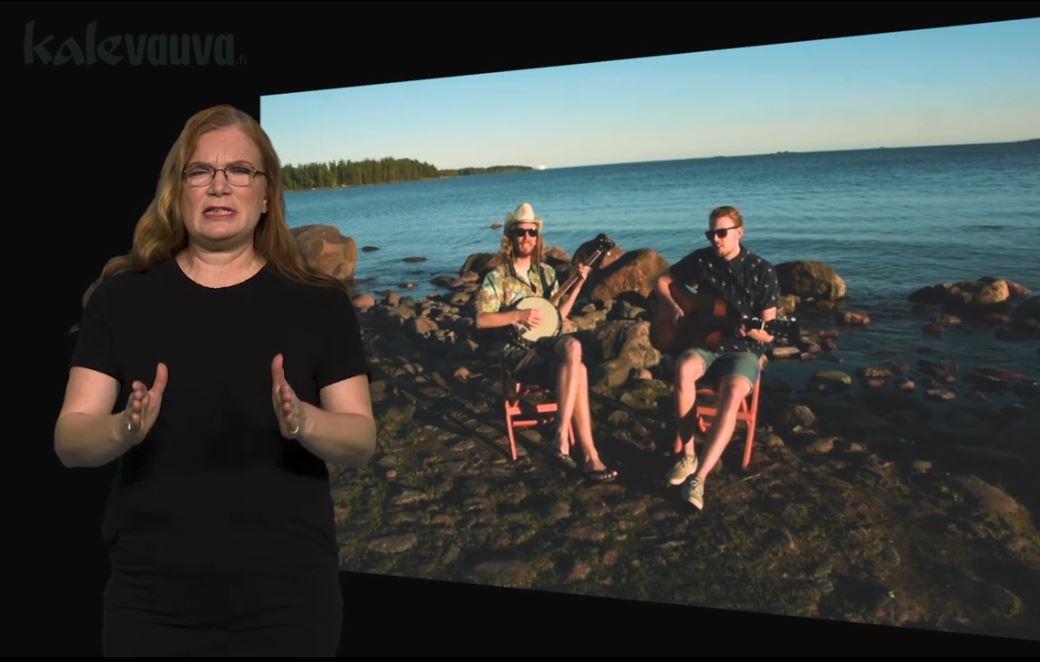 kaksi miestä istuu rannalla tuoleissa soittamassa kitaraa, vasemmassa reunassa nainen viittoo VAKAVA: