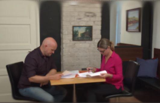Nainen ja mies istuvat pöydän ääressä tutkimassa papereita.