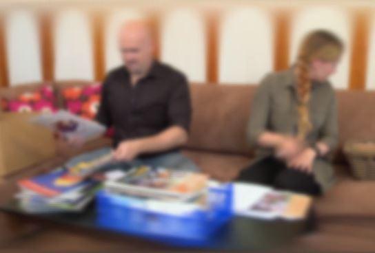 Mies ja nainen istuvat sohvalla vierekkäin ja katsovat eri suuntiin.
