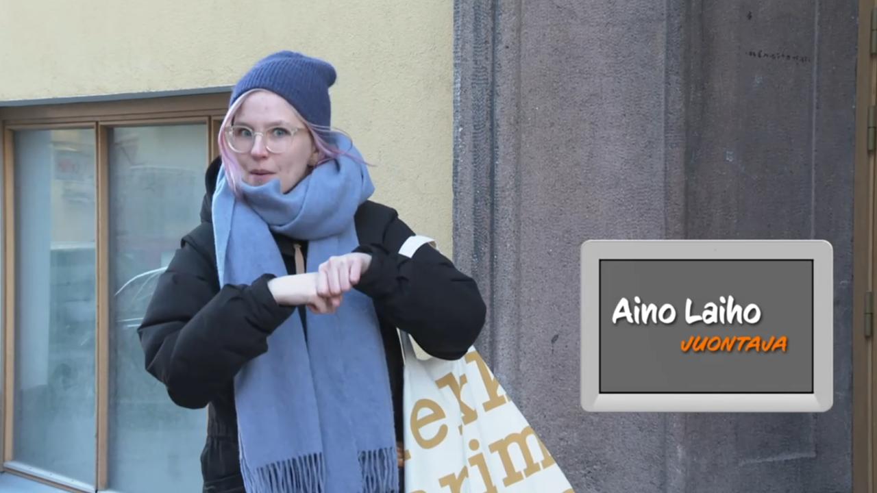 Nainen seisoo kadulla ja viittoo katsoen kameraa