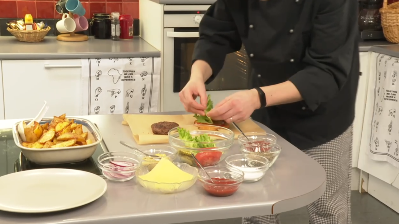Lähikuvassa kädet näkyvät, laittaa salaattia hampurilaiseen.