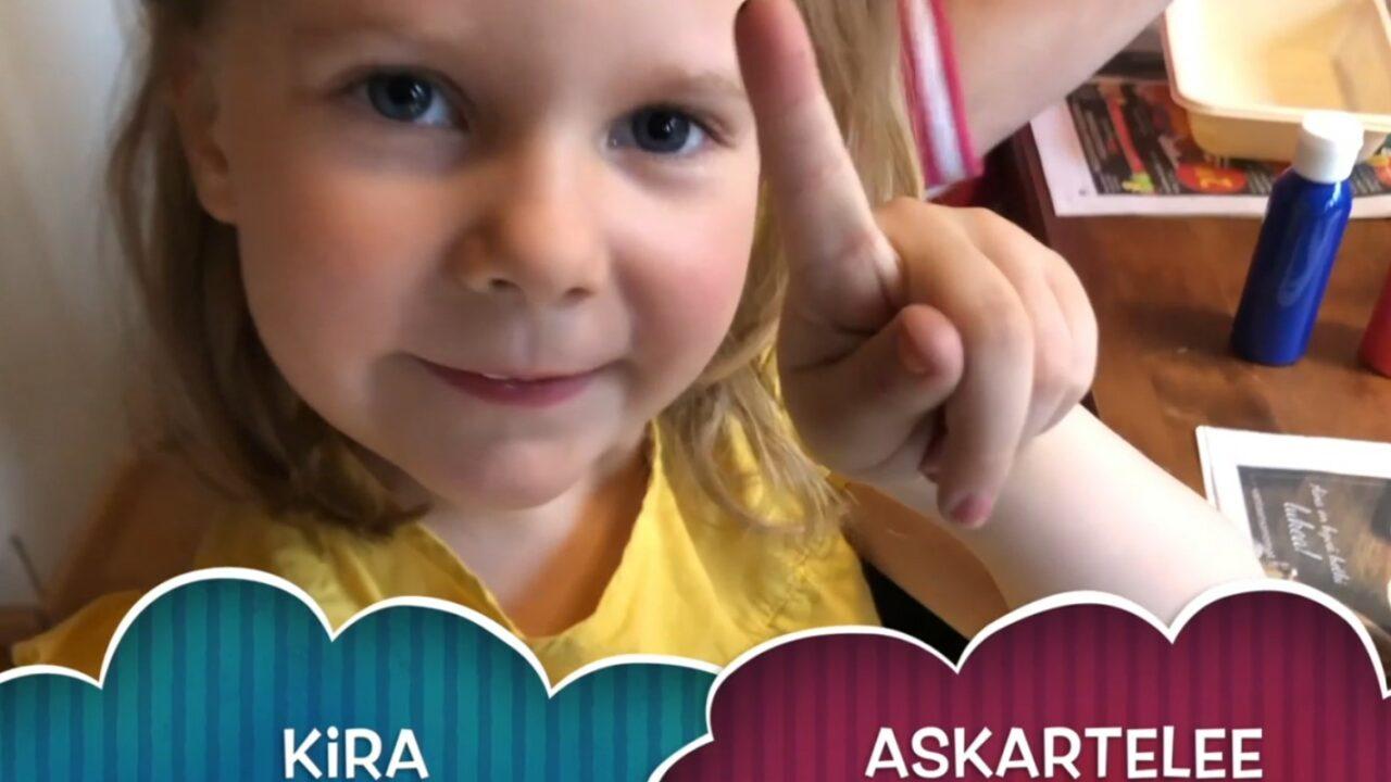 Pieni tyttö keltaisessa paidassa katsoo suoraan kameraan, vasemman käden etusormi on pystyssä.