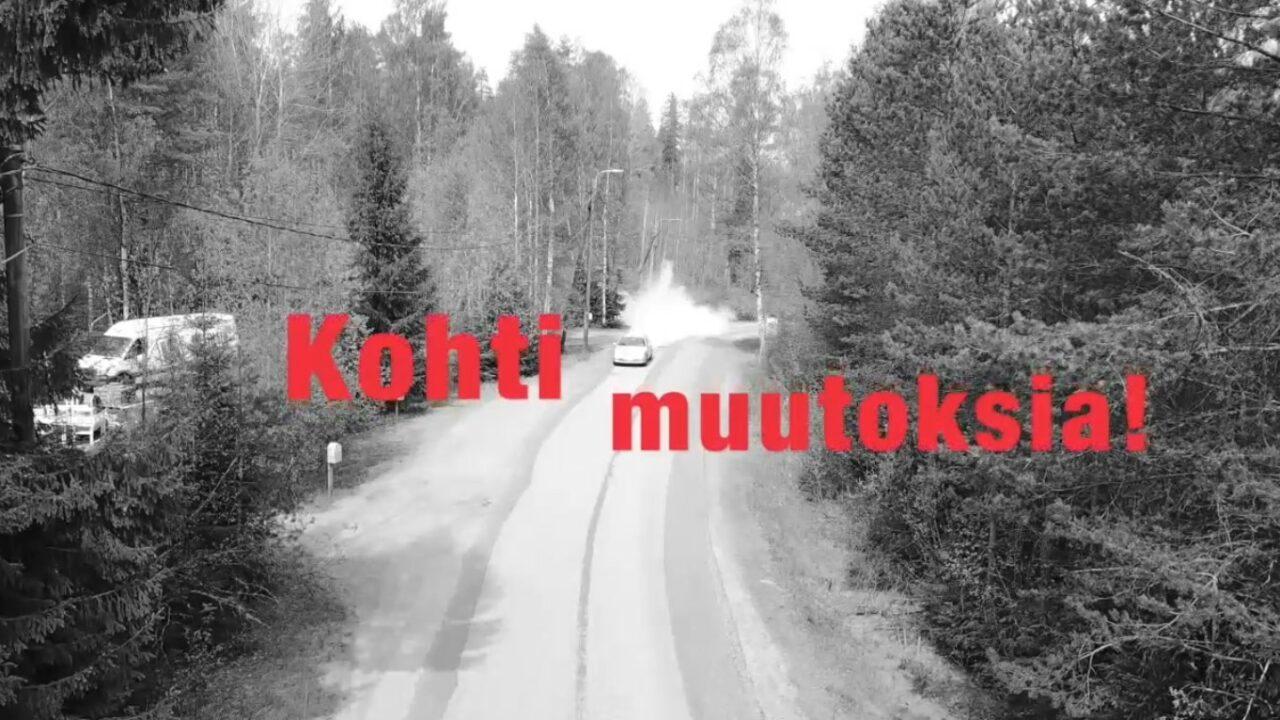 Mustavalkoinen kuva metsästä, jossa keskellä kulkee hiekkatie. Auto kulkee hiekkatietä pitkin. Päällä videon nimi punaisella.