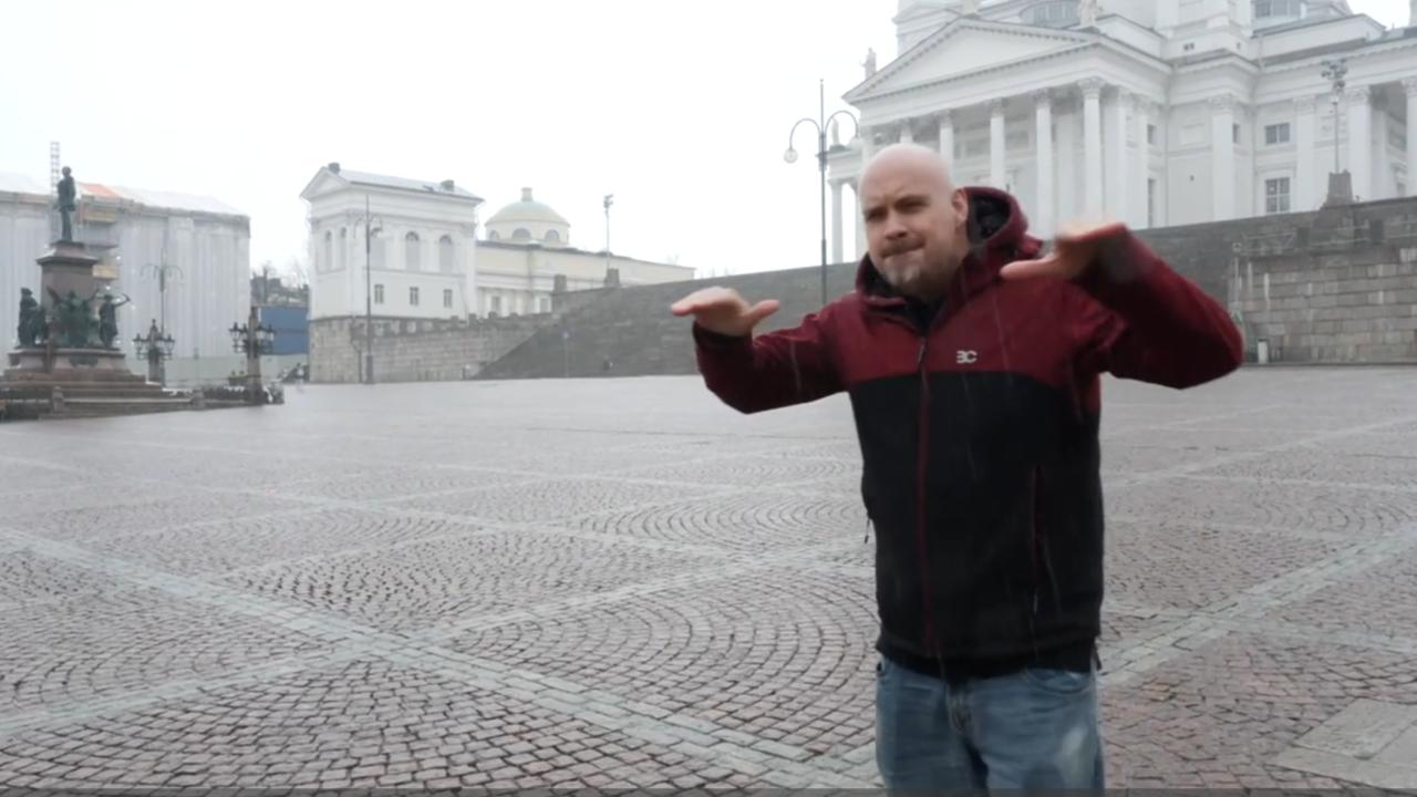 Mies seisoo tyhjällä Senaatintorilla ja viittoo viittoman
