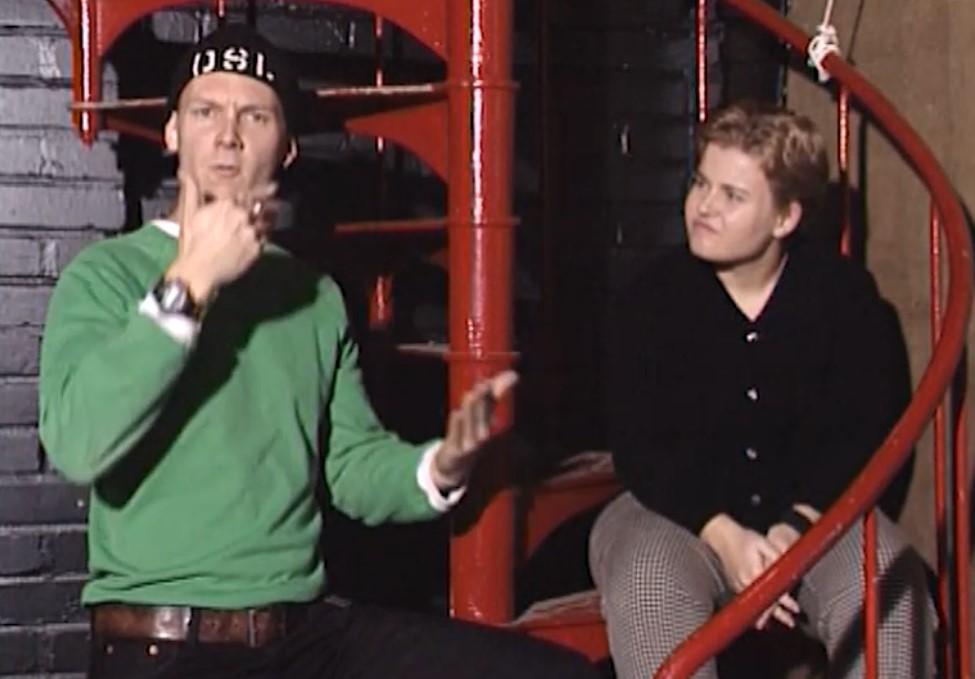 Nuori mies ja nainen punaisilla kierreportailla, mies viittoo.
