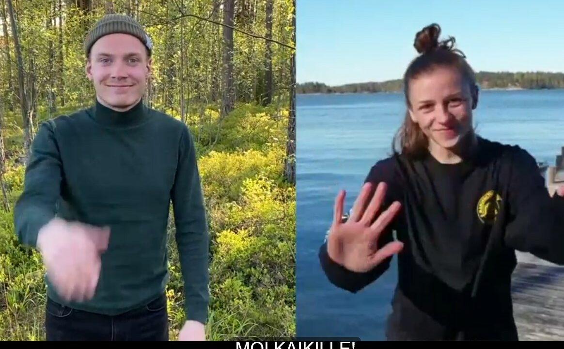 Nuori nainen ja mies viittomassa kameralle, miehen takana metsä, naisen järvimaisema.