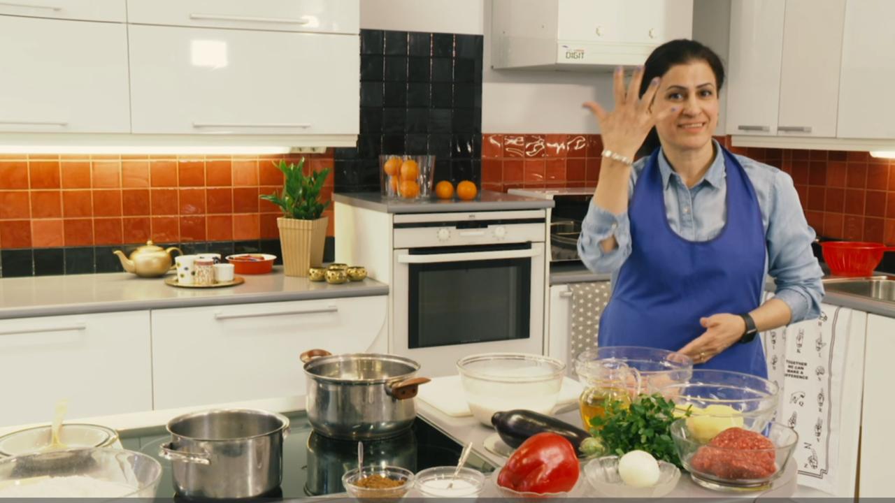 Tummahiuksinen nainen seisoo keittiössä ja näyttää viittomanimensä