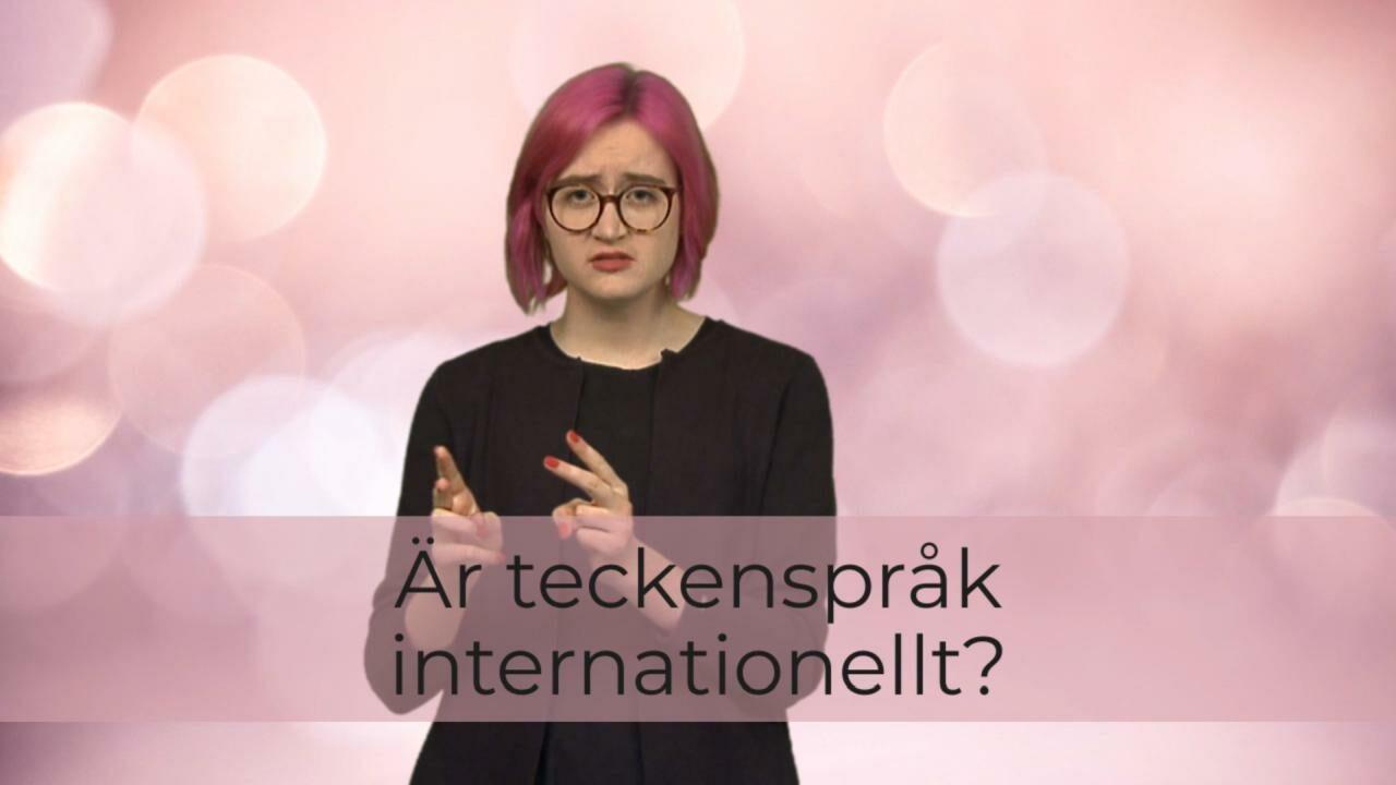 Vaaleanpunaisella taustalla nainen viittomassa, päällä videon nimi tekstinä.