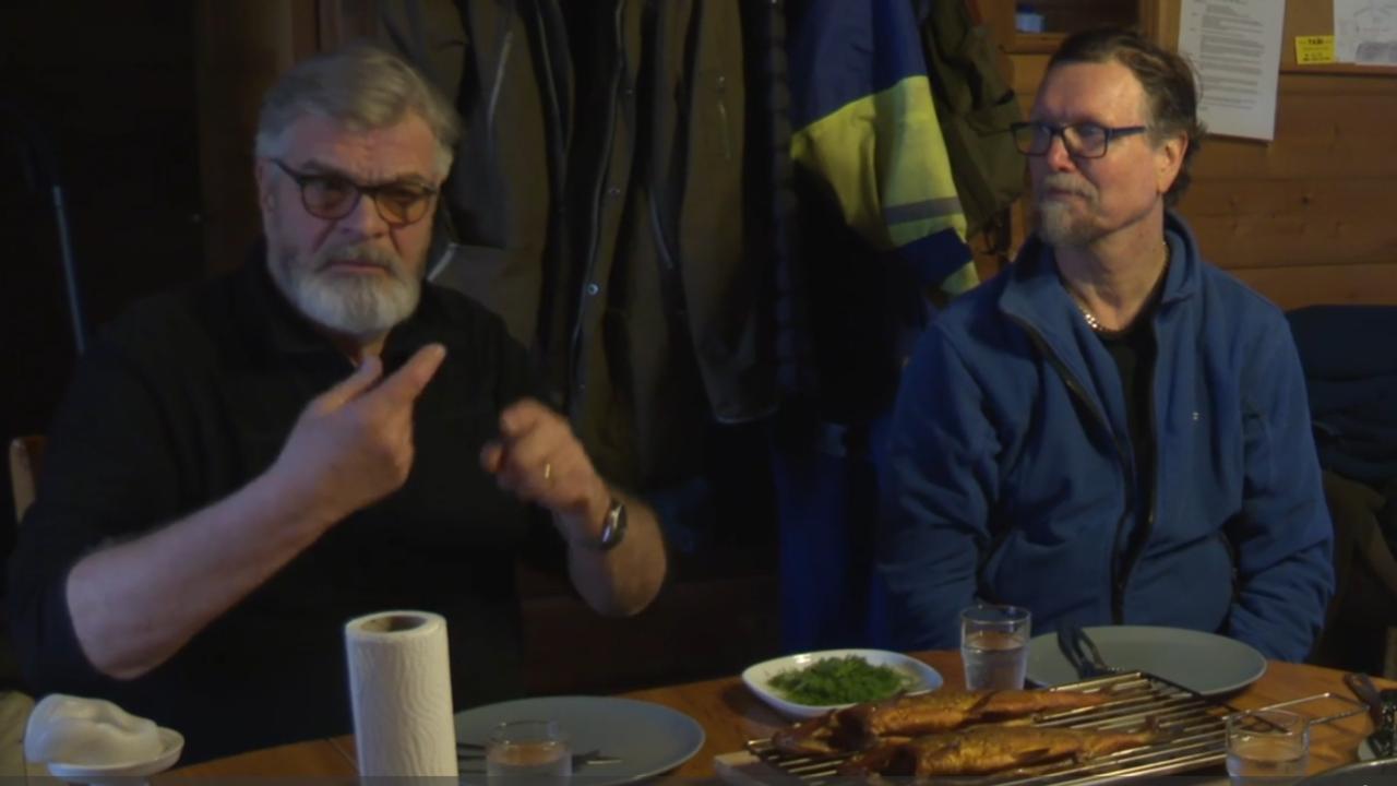 Kaksi iäkkäämpää miestä istuu ruokapöydän äärellä ja toinen viittoo kala