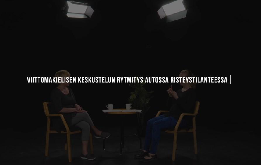 Mustalla pohjalla videon nimi, taustalla näkyy kaksi ihmisen hahmoa.