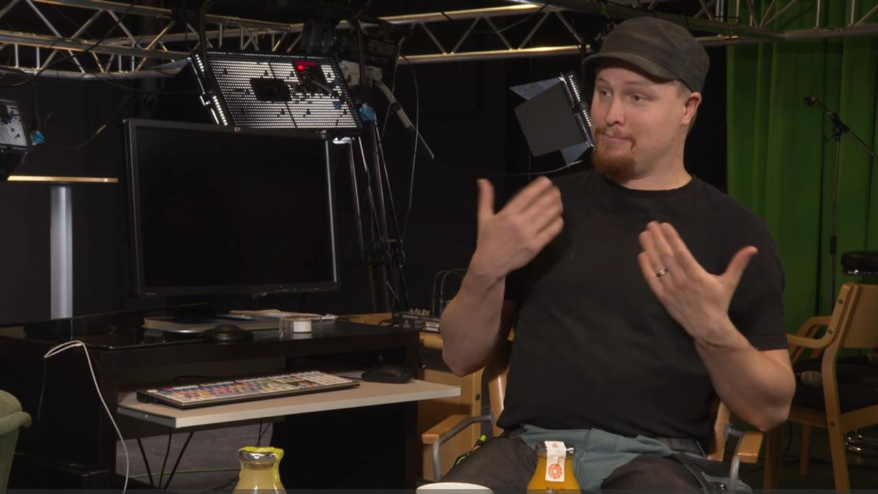 Mies istuu studiolla ja viittoo viittoman