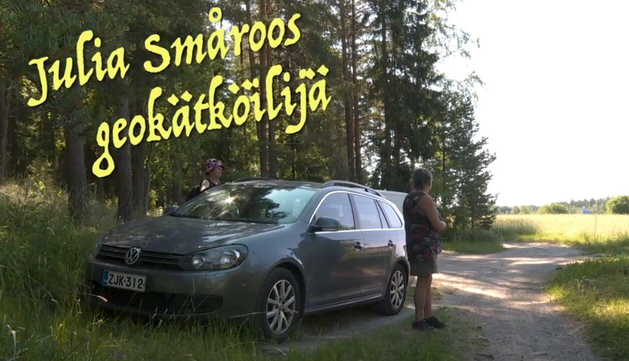 Kesäinen pellonlaita, harmaa auto pysäköitynä ja kaksi naista seisoo auton vierellä.
