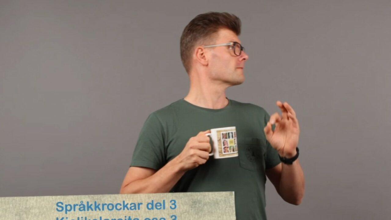 Miehellä kädessä kahvimuki, katsee sivulle ja alla videon nimi.