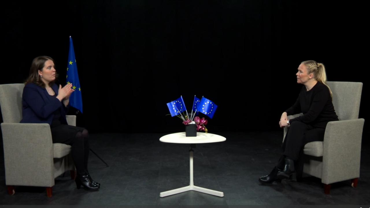Kaksi nuorta naista istuvat studiolla kasvokkain ja toinen viittoo viittoman ihmisoikeus.