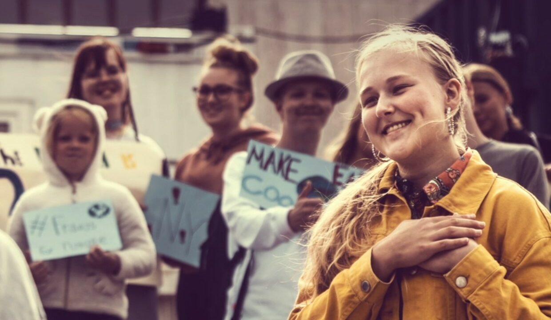 Ryhmä nuoria, edessä nuori nainen viittoo RAKKAUS.