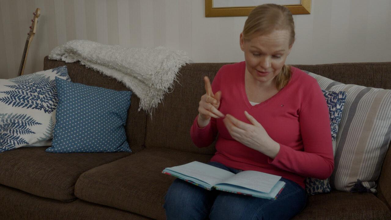 Nainen lukee kirjaa.