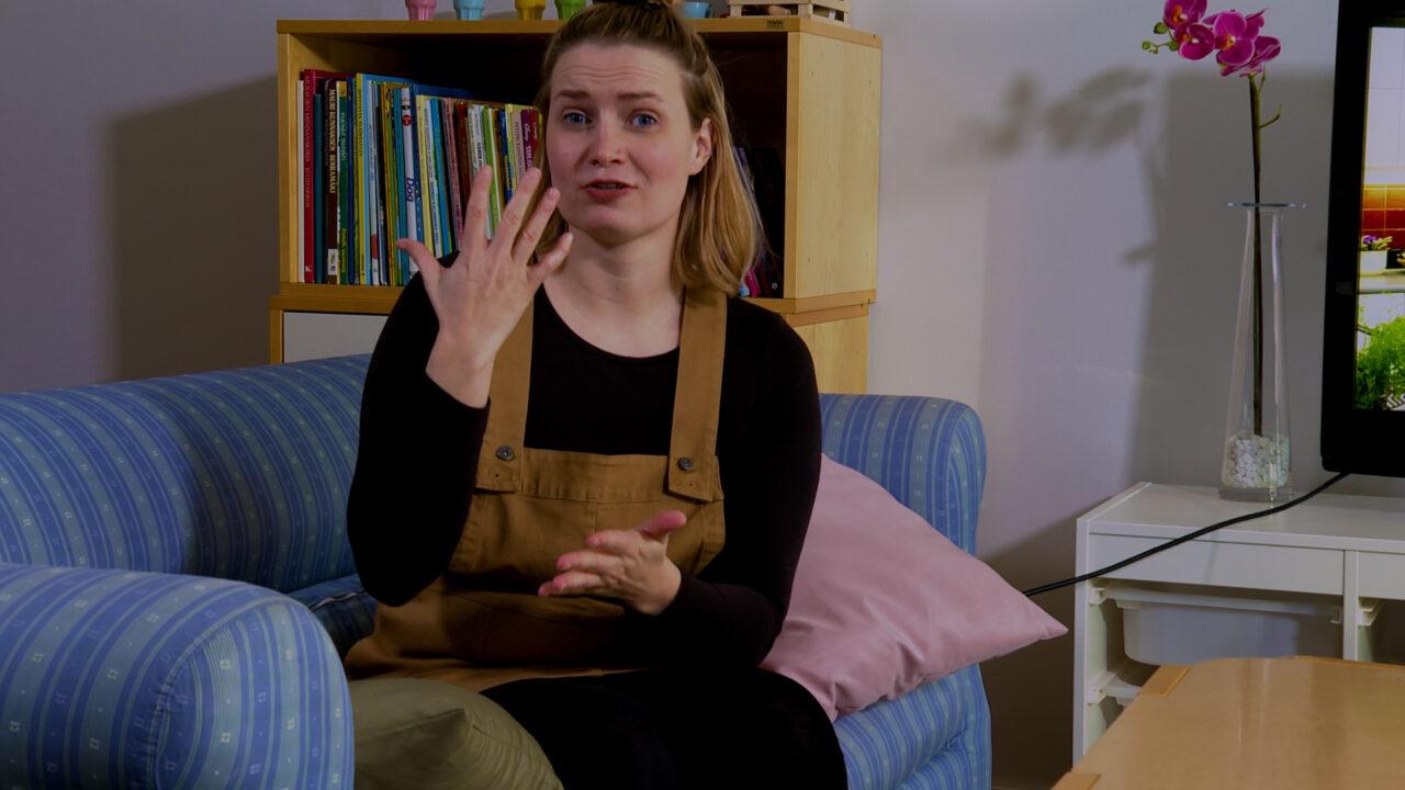Nuori nainen istuu olohuoneen sohvalla ja viittoo viittoman milloin.