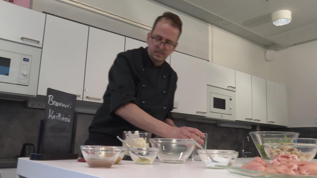 Mies keittiössä pöydän ääressä, edessä useita astioita.