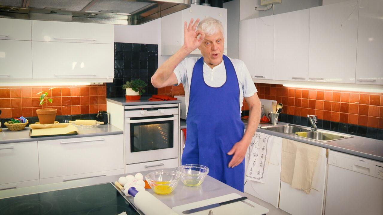 Iäkäs mies seisoo keittiössä essu päällä.