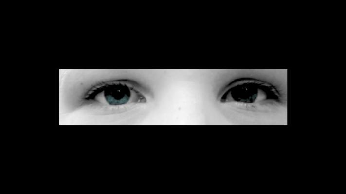 Mustan ruudun keskellä pieni vaakatasoinen rako, josta katsoo silmäpari.